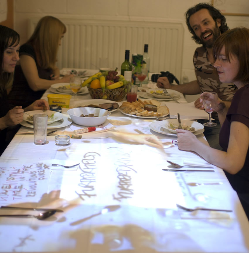 A Barcelona guest writes a message on paper and shares via the tabletop projection with UK guests.